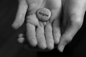Forgive stone offered in the palm of hand